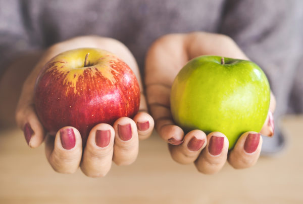 woman hand holding red and green apple