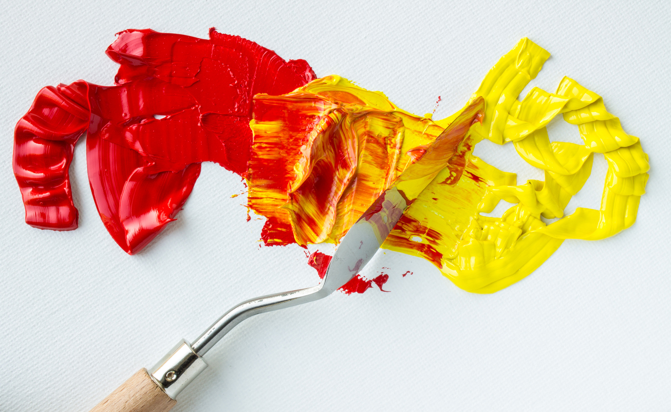Red and yellow paint being mixed with a paintbrush