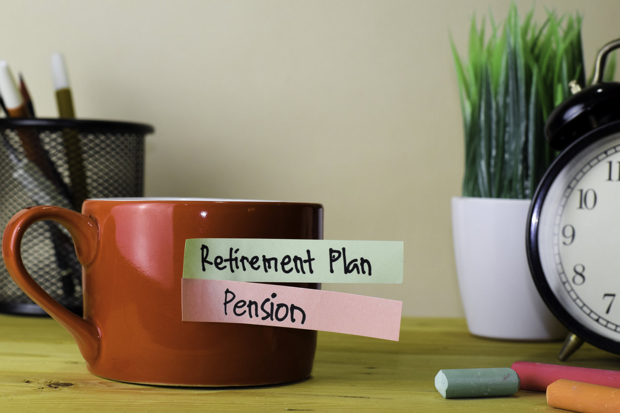 Red mug with post its on reading Retirement Plan and Pension