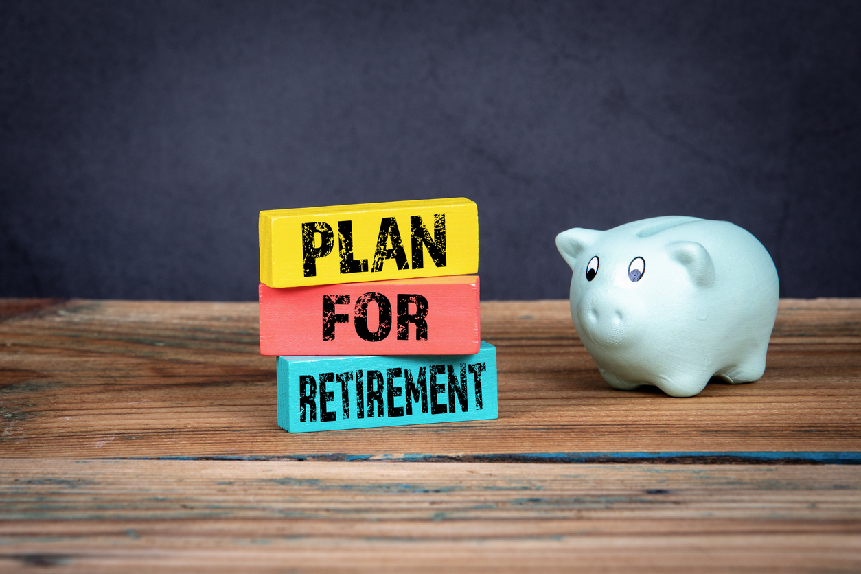 Piggy bank next to three blocks reading Plan For Retirement