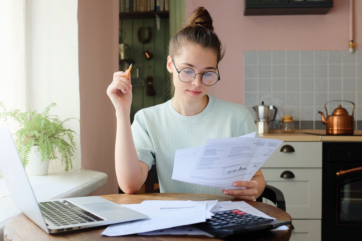 Young woman at table with laptop and documents reviewing her finances