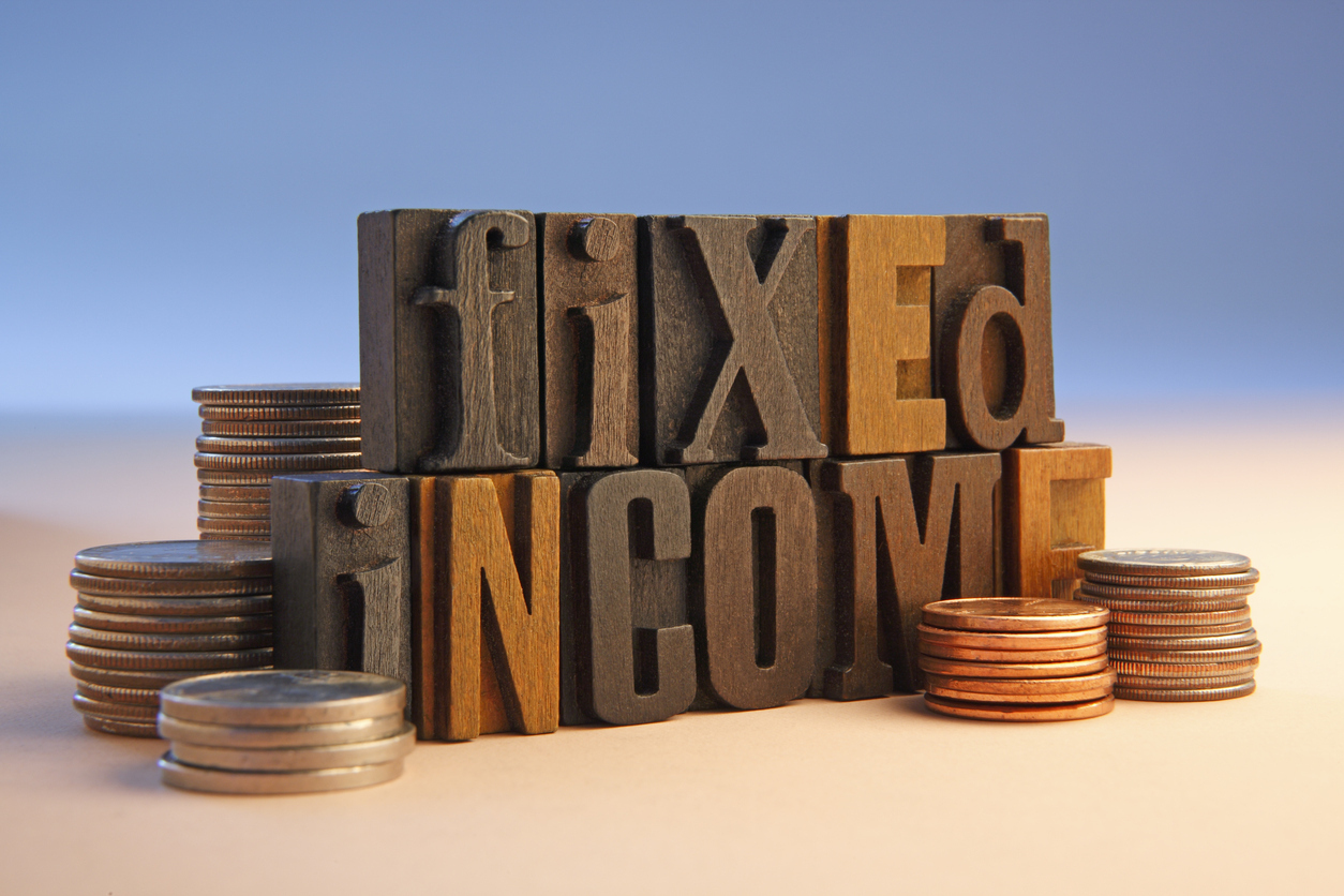 wooden block letters spelling out fixed income with a pile of coins either side
