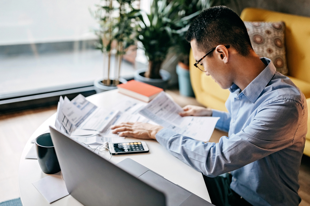 Man calculating finances with laptop and paperwork