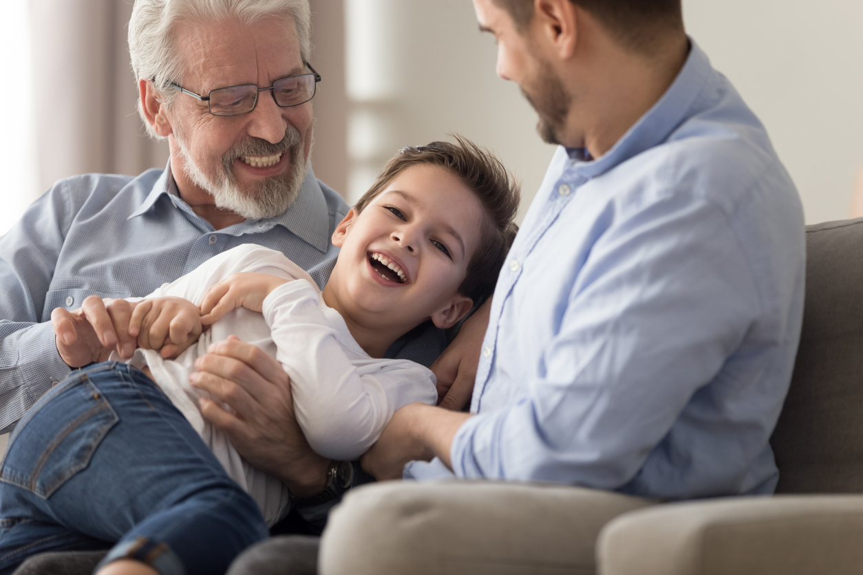 Grandad, Dad, and child playing on the sofa