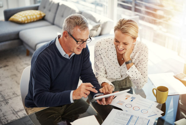 Man and woman at tablet device reviewing finances
